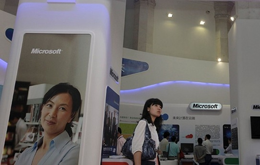 A visitor walks past a Microsoft booth at a computer software expo in Beijing, June 2, 2010. Microsoft Corp appears to be the latest U.S. company targeted by China for anti-trust investigation after government officials paid sudden visits to the software firm's Chinese offices on July 28, 2014. Picture taken June 2, 2010. REUTERS/Stringer (CHINA - Tags: BUSINESS SCIENCE TECHNOLOGY POLITICS) CHINA OUT. NO COMMERCIAL OR EDITORIAL SALES IN CHINA - RTR40GLI