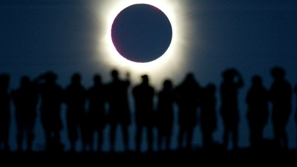 Tourists watch the sun being blocked by the moon during a solar eclipse in the Australian outback town of Lyndhurst, located around 700 kilometres (437 miles) north of Adelaide December 4, 2002. The town is one of only four in Australia where the 26 second-long full eclipse of the sun could be seen and occurred during celebrations for the Year of the Outback. The shadow path of whats called totality, where the 'diamond ring' effect becomes visible, can be seen on a path that is just 36 kilometres wide. REUTERS/David Gray  DG/CP - RTREU1E