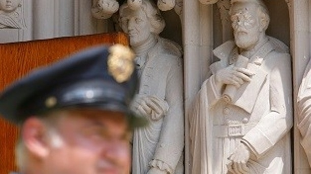 A Duke University security guard keeps watch near the defaced statue of Confederate commander General Robert E. Lee, which stands next to a statue of Thomas Jefferson, at Duke Chapel in Durham, North Carolina, U.S. on August 17, 2017.  REUTERS/Jonathan Drake - RTS1C7L2