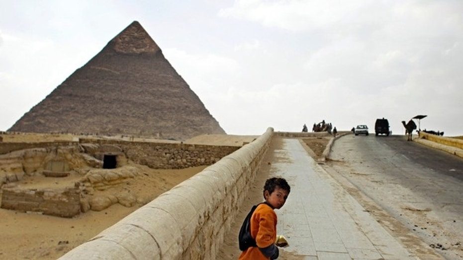 FILE -- In this photo taken Wednesday, March 23, 2011, a young souvenir vendor walks along an almost empty road to the Giza pyramids on the outskirts of Cairo, Egypt.