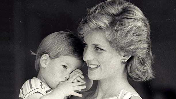 Young Prince Harry tries to hide behind his mother Princess Diana during a morning picture session at Marivent Palace on August 9, 1988, where the Prince and Princess of Wales are holidaying as guests of King Juan Carlos and Queen Sofia.    REUTERS/Hugh Peralta - RTR1JW1G