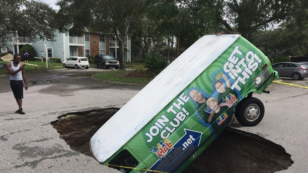 A boy photographs a van in a sinkhole in Winter Springs, Fla., Monday, Sept. 11, 2017, after Hurricane Irma. (Joe Burbank/Orlando Sentinel via AP)