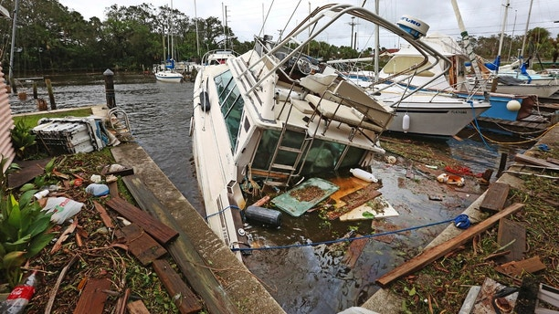 A sinking boat is surrounded by debris in the aftermath of Hurricane Irma at Sundance Marine in Palm Shores, Fla., Monday, Sept. 11, 2017 (Red Huber/Orlando Sentinel via AP)