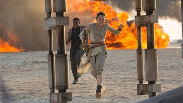 "This photo provided by Disney/Lucasfilm shows Daisy Ridley, right, as Rey, and John Boyega as Finn, in a scene from the film, ""Star Wars: The Force Awakens,"" directed by J.J. Abrams. The movie opens in U.S. theaters on Friday, Dec. 18, 2015. (David James/Disney/Lucasfilm via AP)"