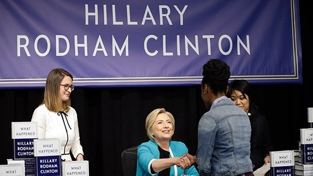 "Hillary Rodham Clinton, center, greets people who waited in line of a signed copy of her book ""What Happened"" at a book store in New York, Tuesday, Sept. 12, 2017. (AP Photo/Seth Wenig)"