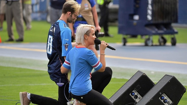 Sep 24, 2017; Nashville, TN, USA; Recording artist Meghan Linsey kneels after singing the national anthem before the game between the Tennessee Titans and the Seattle Seahawks at Nissan Stadium. Mandatory Credit: Jim Brown-USA TODAY Sports - 10305030