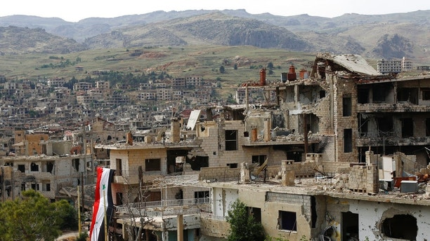 FILE - In this May 18, 2017 file photo, a Syrian National flag hangs out of a damaged building at the mountain resort town of Zabadani in the Damascus countryside, Syria. The Syrian government on Tuesday, June 27, 2017 dismissed White House allegations that it was preparing a new chemical weapons attack, as activists reported an airstrike on an Islamic State-run jail in eastern Syria that they said killed more than 40 prisoners. (AP Photo/Hassan Ammar, File)