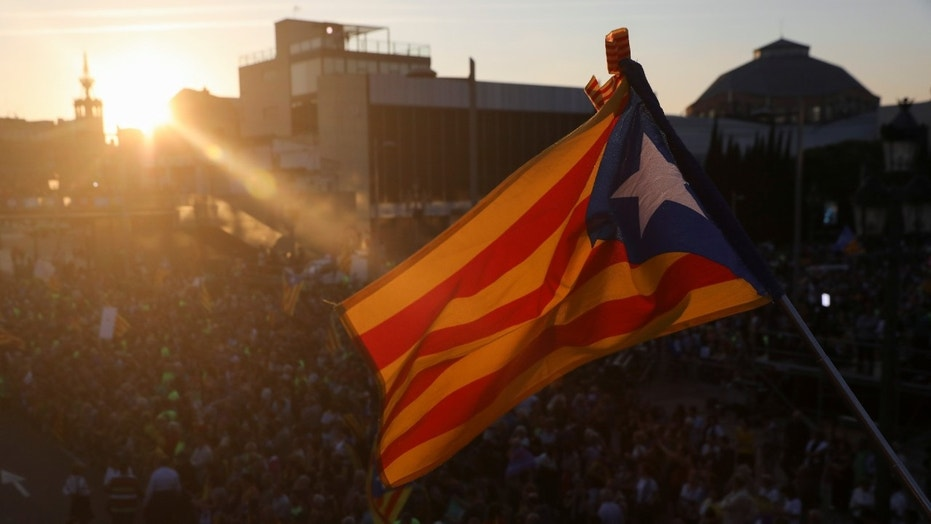 A woman holds an Estelada (Catalan separatist flag) as she waits for a closing rally in favour of the banned October 1 independence referendum in Barcelona, Spain September 29, 2017.