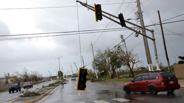 Cars drive past a damaged traffic light after the area was hit by Hurricane Maria en Guayama, Puerto Rico September 20, 2017. REUTERS/Carlos Garcia Rawlins - RC16CFE9C660