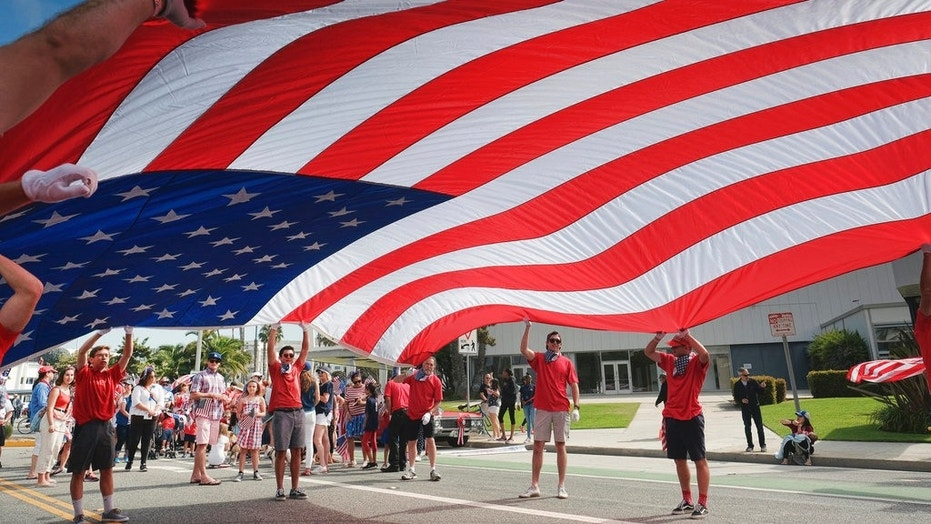 FILE -- Participants carry an American flag during the 4th of July parade in Santa Monica, Calif. on Tuesday, July 4, 2017.