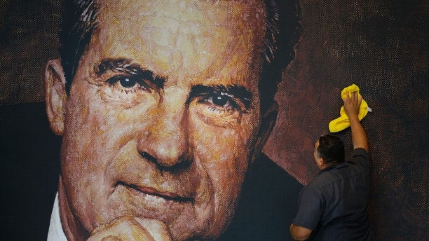 In this Wednesday, Oct. 5, 2016 photo, Tayron Santos cleans the newly-installed wall mural of former President Richard Nixon in the lobby area of the Richard Nixon Presidential Library and Museum in Yorba Linda, Calif. The museum will reopen Friday, Oct. 14, following a $15 million makeover aimed at bringing the country's 37th president closer to younger generations less familiar with his groundbreaking trip to China or the Watergate scandal. (AP Photo/Jae C. Hong)