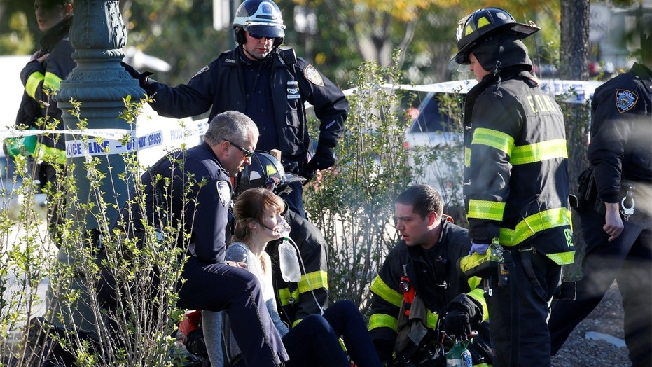 A woman is aided by first responders after sustaining injury on a bike path in lower Manhattan in New York, NY, U.S., October 31, 2017.  REUTERS/Brendan McDermid - RC14C171D340
