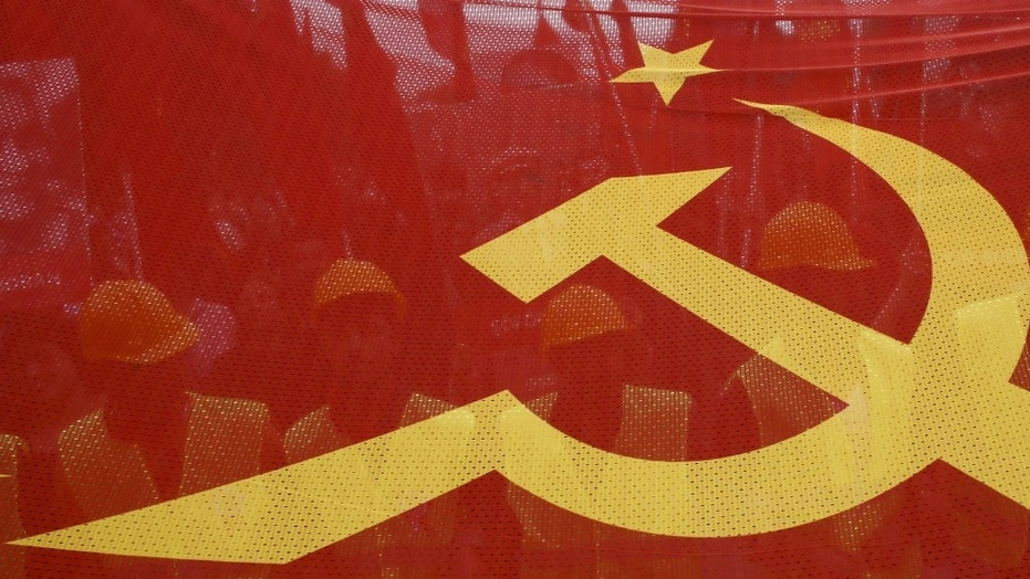 FILE - -People walk behind a red banner with hammer and sickle symbols during a May Day rally in Istanbul, Turkey, May 1, 2016.