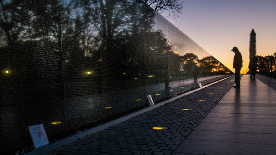 FILE -- A visitor at the Vietnam War Memorial in Washington passes early in the morning on Veterans Day, Monday, Nov. 11, 2013, to look at the names inscribed on the wall.