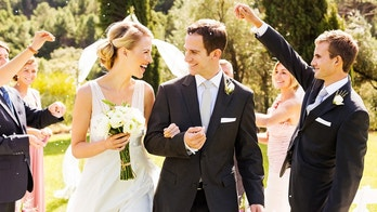 Wedding guests throwing confetti on newlywed couple during outdoor wedding. Horizontal shot.