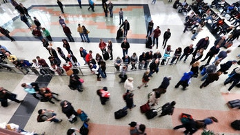 On the busiest travel day of the year, family and friends watch for arrivals of loved ones, at Denver International Airport, Wednesday, Nov. 27, 2013. Denver's airport was busy Wednesday with holiday travelers but storms on the East Coast did not ripple out into the widespread meltdown that had been feared. (AP Photo/Brennan Linsley)