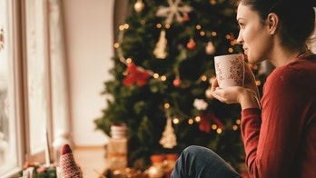 Young woman drinking tea by the Christmas tree, looking through window.
