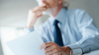 Pensive businessman with hand on chin looking away and holding a document, selective focus, glasses on foreground