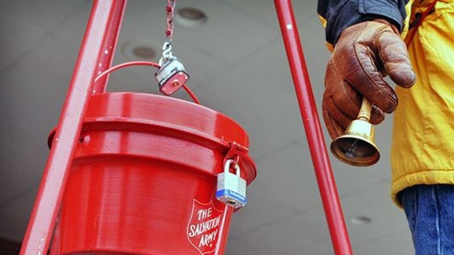 FILE -- Salvation Army donation kettles and bell ringer.