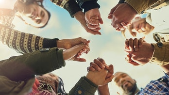 Shot of a group of friends putting their hands together in prayer