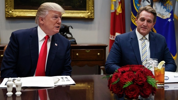 Sen. Jeff Flake, R-Ariz., right, listens as President Donald Trump speaks before hosting a lunch with Senate Republicans in the Roosevelt Room of the White House, Tuesday, Dec. 5, 2017, in Washington. (AP Photo/Evan Vucci)