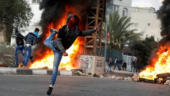 A Palestinian demonstrator hurls stones toward Israeli troops during clashes at a protest against U.S. President Donald Trump's decision to recognize Jerusalem as the capital of Israel, near the West Bank city of Nablus, December 29, 2017. REUTERS/Mohamad Torokman - RC12B4068BC0