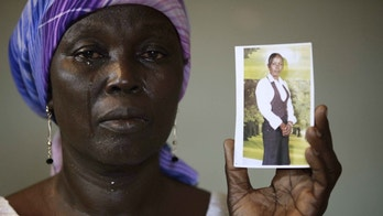 In this photo taken on Monday, May 19, 2014.  Martha Mark, the mother of kidnapped school girl Monica Mark cries as she display her photo, in the family house, in Chibok, Nigeria. More than 200 schoolgirls were kidnapped from a school in Chibok in Nigeria's north-eastern state of Borno on April 14. Boko Haram claimed responsibility for the act. (AP Photo/Sunday Alamba)