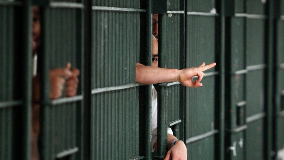 Inmates flash hand signals at the Men's Central Jail in downtown Los Angeles Wednesday, Oct. 3, 2012. Los Angeles County Sheriff Lee Baca says he plans to implement all the reforms suggested by a commission in the wake of allegations that a culture of violence flourished in his jails. (AP Photo/Reed Saxon)