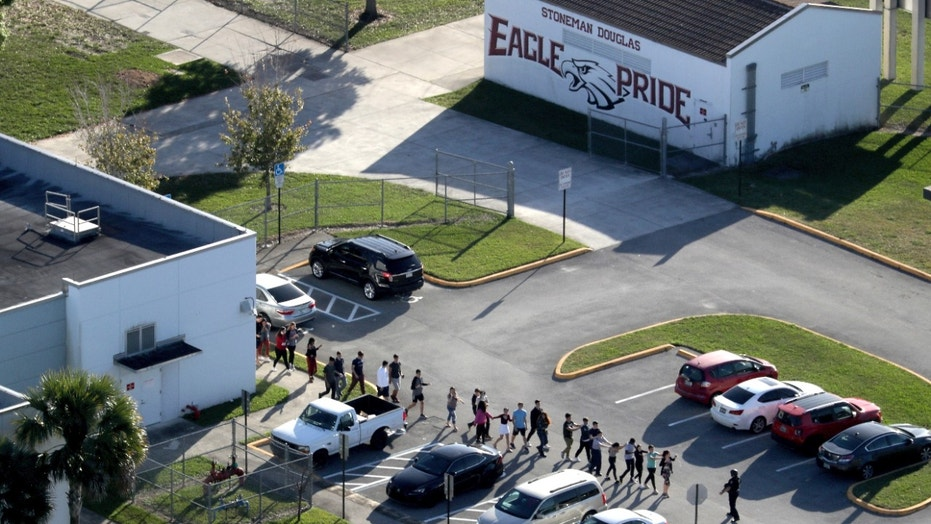 Students are evacuated by police from Marjory Stoneman Douglas High School in Parkland, Fla., on Wednesday, Feb. 14, 2018.