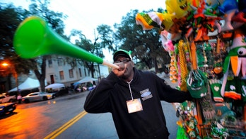 Street vendor Marshall Baker blows a horn to attract customers before the start of Savannah's 190-year-old St. Patrick's Day parade, Monday, March 17,  2014, in Savannah, Ga. Started in 1824 by early Irish immigrants to Georgia, the parade has ballooned into a sprawling street party that makes for one of Savannah's most profitable tourism events. (AP Photo/Stephen B. Morton)