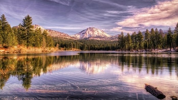 Lassen Peak, in the Lassen Volcanic National Park, shows signs of the first winter snow. In the foreground is Manzanita lake, which is a fly fisherman paradise.