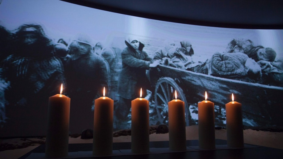 FILE -- Memorial candles are lit in front of a photo taken during WWII showing refugees fleeing from the Nazis.