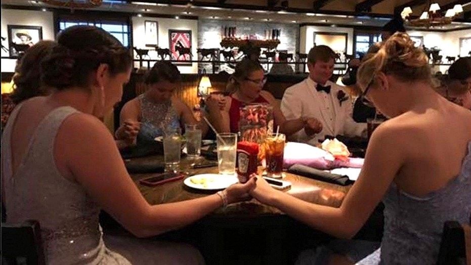 A group of students holding hands while saying grace before prom.