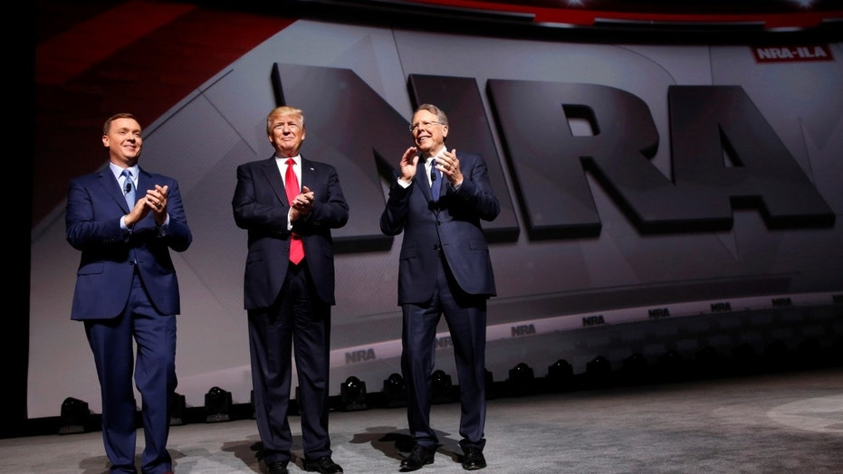 FILE --  April 28, 2017: NRA Executive Director Chris Cox (L) and Executive Vice President and CEO Wayne LaPierre (R) welcome President Donald Trump (C) onstage to deliver remarks at the National Rifle Association (NRA) Leadership Forum at the Georgia World Congress Center in Atlanta, Georgia.