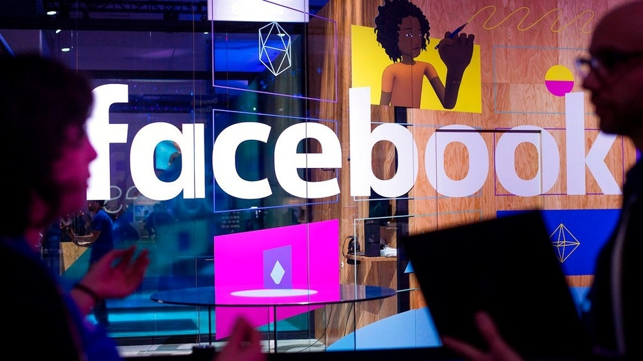 FILE - In this April 18, 2017, file photo, conference workers speak in front of a demo booth at Facebook's annual F8 developer conference, in San Jose, Calif.