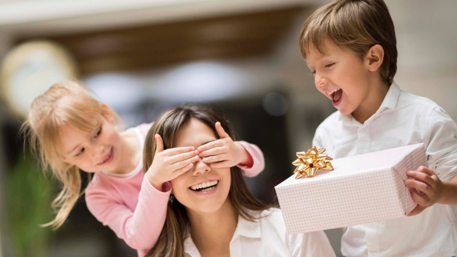 Happy kids surprising mom with a gift on mother's day