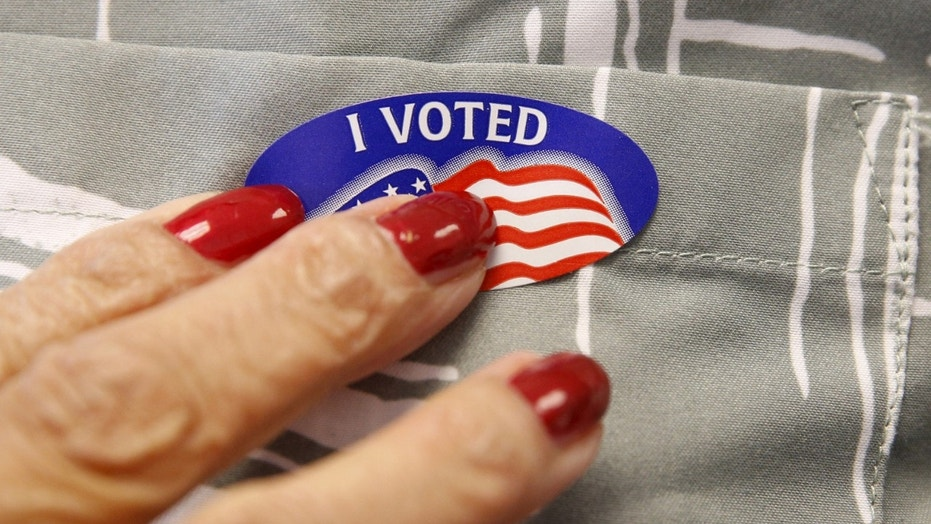 FILE -- Woman receives voting sticker.