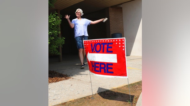 Cindy Benton celebrates after voting in the Arkansas primary election on Tuesday, May 22, 2018 in Little Rock, Ark. The Democratic and Republican parties held elections Tuesday, while all registered voters were allowed to vote in judicial elections. (AP Photo/Kelly P. Kissel)