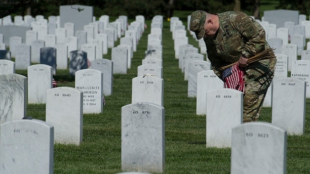 Army Chief of Staff Gen. Mark Alexander Milley places flags at gravesite as the Army 3d U.S. Infantry Regiment, The Old Guard, honor the nation's fallen military heroes during its annual Flags In ceremony at Arlington National Cemetery, May 24, 2018. (AP Photo/Cliff Owen)