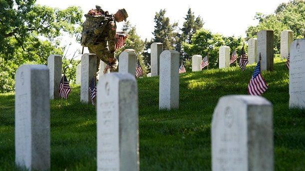 A member of the Army 3d U.S. Infantry Regiment, The Old Guard, places a flag at the headstone of fallen military member during its annual Flags In ceremony at Arlington National Cemetery, Thursday, May 24, 2018, in Arlington, Va. (AP Photo/Cliff Owen)