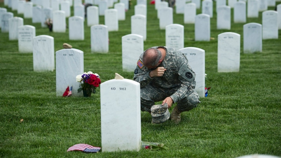 FILE -- Army Col. Matthew Rasmussen, of the Army Military District of Washington, wipes tears from his eyes while visiting the grave of Army Staff Sgt. Richard Tieman, 28, of Waynesboro, Pa.