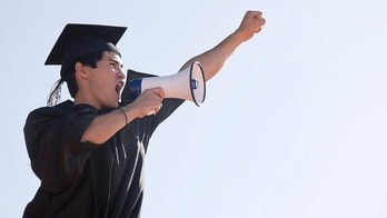 Graduate giving speach with his hand up in the air. Graduation