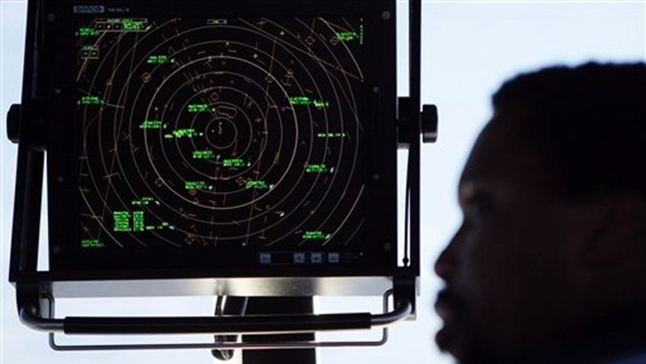 FILE - An air traffic controller stands beneath a radar screen in the control tower at Washington's Reagan National Airport.