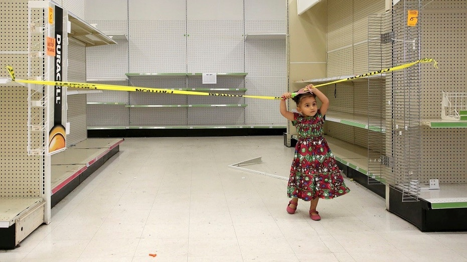 FILE -- Two-year-old Sparrow Simon plays in an empty isle of the Toys R Us store, Thursday, June 28, 2018, in Houston.