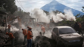 """Rescue workers remove piles of ash spewed by the Volcan de Fuego, or """"Volcano of Fire,"""" eruption, in El Rodeo, Guatemala, Wednesday, June 6, 2018. Wednesday morning rescuers were concerned about possible dangers posed not only by more volcanic flows but also rain. Authorities have said the window is closing on the chances of finding anyone else alive in the devastation. (AP Photo/Rodrigo Abd)"""