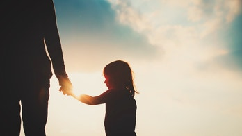silhouette of little girl holding parent hand at sunset, parenting concept