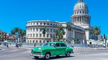 Old American car driving at a street of old Havana, Cuba
