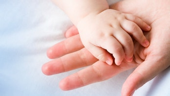Image of mom's palm with newborn baby hand on its surface