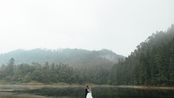 A romantic latin newlywed couple standing and kissing outdoors in a foggy day in a horizontal full length shot.