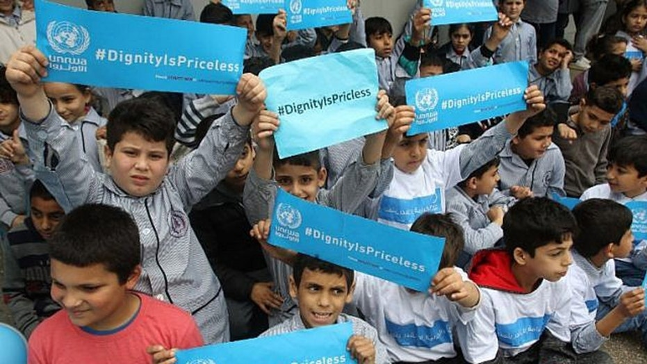 FILE -- Palestinian children hold placards at a school belonging to the United Nations Relief and Works Agency for Palestine Refugees (UNRWA) in the town of Sebline east of the southern Lebanese port of Saida, on March 12, 2018, during a protest against U.S. aid cuts to the organization.